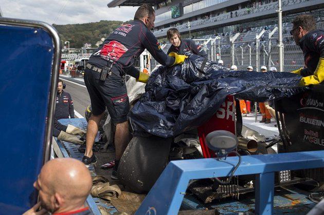 Mechanici stáje Toro Rosso v boxech odkrývají zničenou formuli Carlose Sainze.