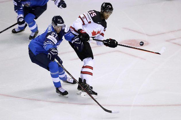 Finský hokejový reprezentant Eetu Luostarinen a Kanaďan Darnell Nurse v akci během úvodního zápasu mistrovství světa.