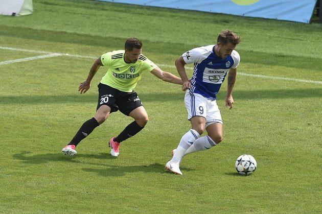 Tomáš Ladra z Mladé Boleslavi si kryje míč před Lubošem Tusjakem z Karviné.