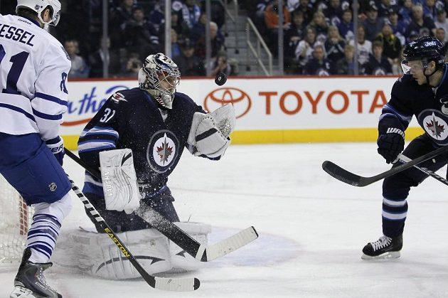 Brankář Winnipegu Ondřej Pavelec se natahuje po puku v utkání s Torontem.
