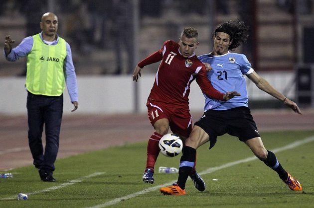 Uruguayský útočník Edinson Cavani (vpravo) bojuje o míč s Odayem Zahranem z Jordánska v úvodním barážovém duelu o postup na MS.