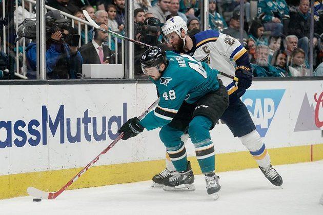 Tomáš Hertl ze San Jose Sharks vede puk podél mantinelu před obráncem St. Louis Blues Alexem Pietrangelem během pátého zápasu semifinálové série NHL.