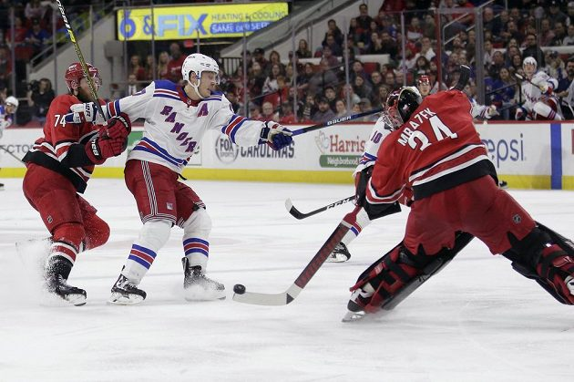 Český gólman Caroliny Hurricanes Petr Mrázek (34) rozehrává puk během utkání NHL.
