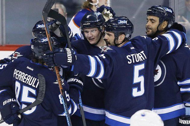 Hokejisté Winnipegu slaví gól proti Edmontonu. Zleva Mathieu Perreault (č. 85), Evander Kane, Jacob Trouba, Mark Stuart a Dustin Byfuglien.