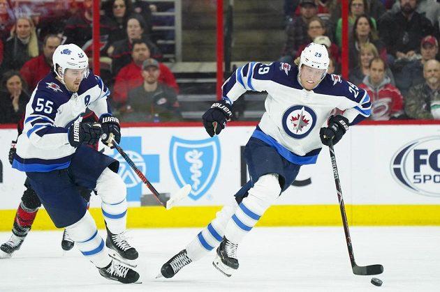 Mark Scheifele (vlevo) a finský rychlík Patrick Laine rozjíždějí akci Winnipegu v utkání NHL na ledě Caroliny.