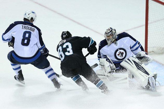 Útočník San Jose Matt Nieto (č. 83) se snaží prostřelit brankáře Winnipegu Ondřeje Pavelce.
