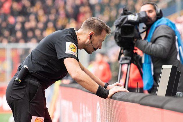 Rozhodčí Karel Hrubeš zkoumá video po zákroku Florina Nity na Josefa Hušbauera během Slavia - Sparta.