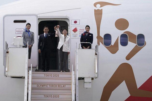 Olympijský oheň je v Japonsku. Trojnásobný olympijský vítěz Tadahiro Nomura (vlevo) a držitelka tří zlatých medailí Saori Jošidaová s olympijským ohněm po příletu do pořadatelské země olympiády.