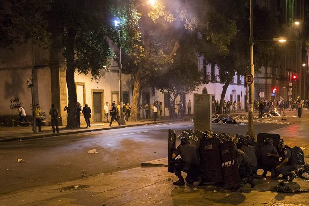 Policisté se kryjí za štíty před demonstranty v Rio de Janeiru.