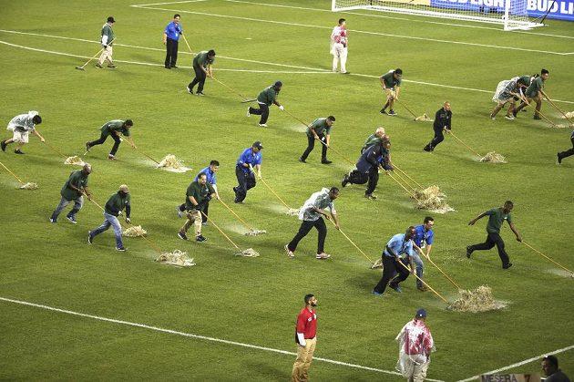 Každá ruka dobrá. Pořadatelé na Copě América odklízí vodu z trávníku na stadiónu Soccer Field v Chicagu.