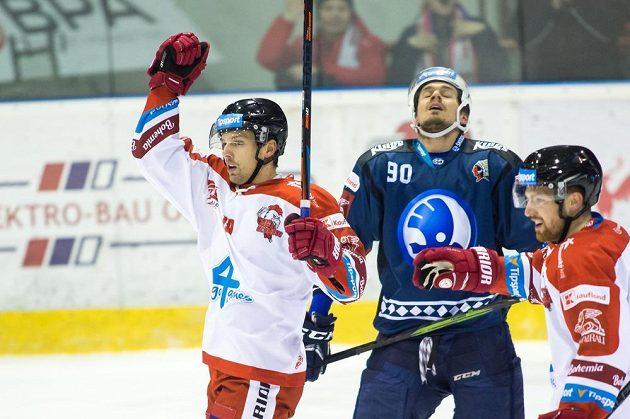 Olomoucký hokejista Lukáš Nahodil se raduje, zklamaný Roman Vráblík z Plzně všemu během extraligového utkání jen přihlíží.