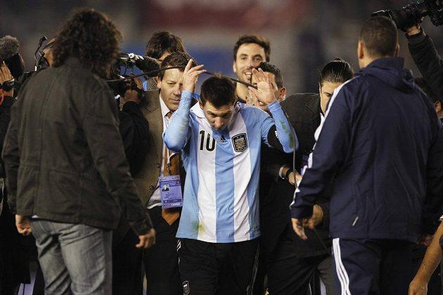 Útočník Lionel Messi se proplétá skrz argentinské novináře do kabin.