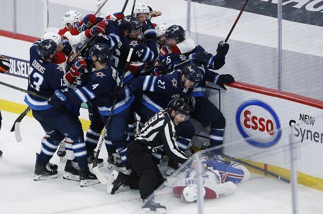 Zraněný útočník Montrealu Canadiens Jake Evans (71) leží zraněný na ledové ploše po zákroku Marka Scheifeleho (55) z Winnipegu Jets během utkání play off NHL. Na ledě se strhla okamžitě rvačka.