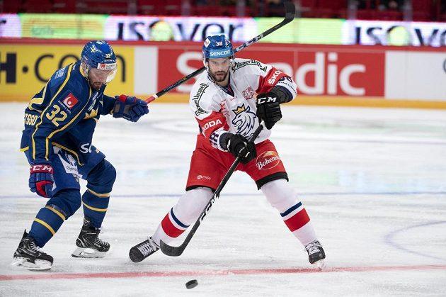Český forvard Tomáš Hyka nahazuje puk do útočné třetiny, vlevo sleduje jeho počínání Lukas Bengtsson ze Švédska.