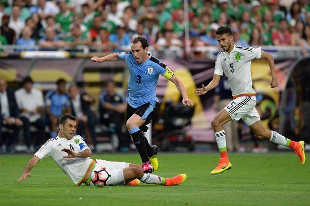 Kapitán Uruguaye Diego Godín (3) a mexičtí obránci Diego Reyes (5) s Rafaelem Márquezem.