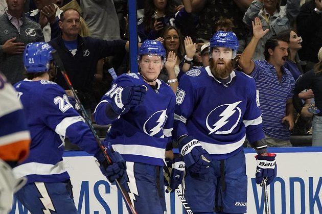 Český útočník Ondřej Palát se trefil do sítě New York Islanders v semifinále NHL a jeho Tampa vyhrála zápas vysoko 8:0. Palát oslavuje svou trefu se spoluhráči Braydenem Pointem (21) a obráncem Davide Savardem.