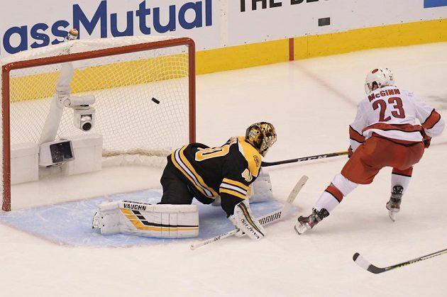 Hokejista Caroliny Brock McGinn překonává brankáře Bostonu Tuukka Raska v prvním kole Stanley Cupu.