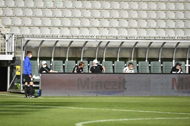 Členové realizačního týmu Zlína dodržují na střídačce během utkání fotbalové ligy v Jablonci potřebné rozestupy.