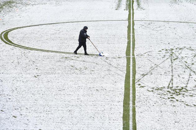 Pořadatel upravuje zasněžené hřiště před začátkem zápasu Jablonec - Příbram.