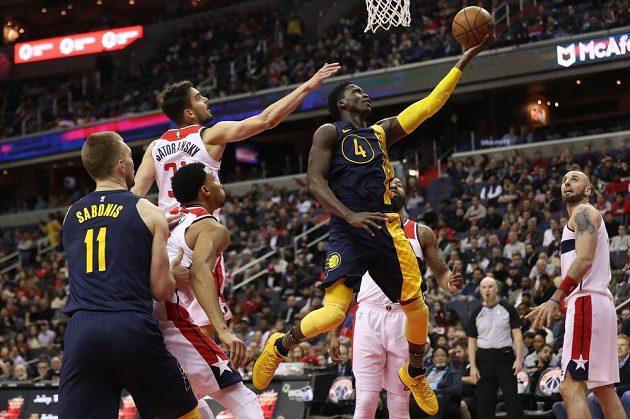 Victor Oladipo (4) z Indiany Pacers střílí na koš Washingtonu Wizards v utkání NBA, zabránit se mu ve skórování snaží Tomáš Satoranský (31).