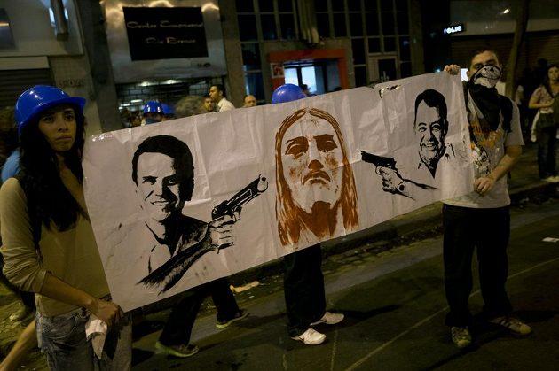 Guvernér Rio de Janeira Sergio Cabral (vlevo) a starosta Eduardo Paes na plakátu míří zbraněmi na Ježíše Krista, symbol brazilského města.