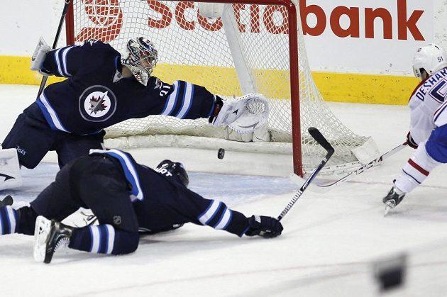Brankář Ondřej Pavelec se marně natahuje po puku, vystřeleném Davidem Desharnaisem z Montrealu.