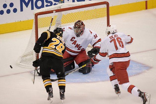 Gólman Caroliny Petr Mrázek (34) kryje střelu Ondřeje Kašeho z Bostonu v 1. kole Stanley Cupu.