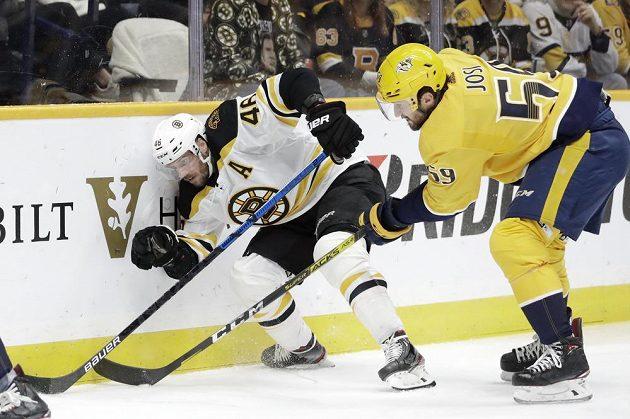 Český útočník Bostonu David Krejčí čelí ataku Romana Josiho z Nashville Predators v utkání NHL.