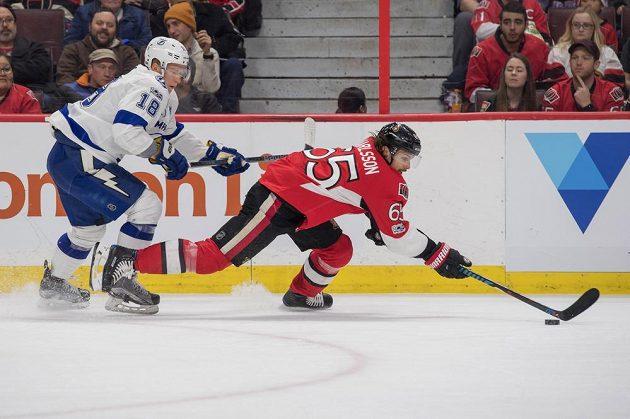Český útočník Ondřej Palát z Tampy Bay se snaží atakovat unikajícího obránce Ottawy Senators Erika Karlssona v utkání NHL s Ottawou Senators. Palát gól nedal, ale měl asistenci u vítězné trefy svého týmu.