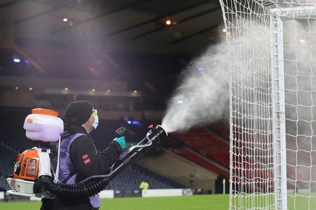 Jeden z pořadatelů dezinfikuje vybavení hřiště před utkáním Skotsko - ČR v Hampden Parku.
