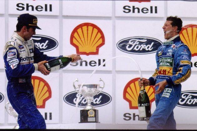 Damon Hill (vlevo) sprchuje šampaňským Michaela Schumachera po Velké ceně Brazílie v roce 1994. Po kolizi v posledním závodu sezóny by si oba spíš vjeli do vlasů.