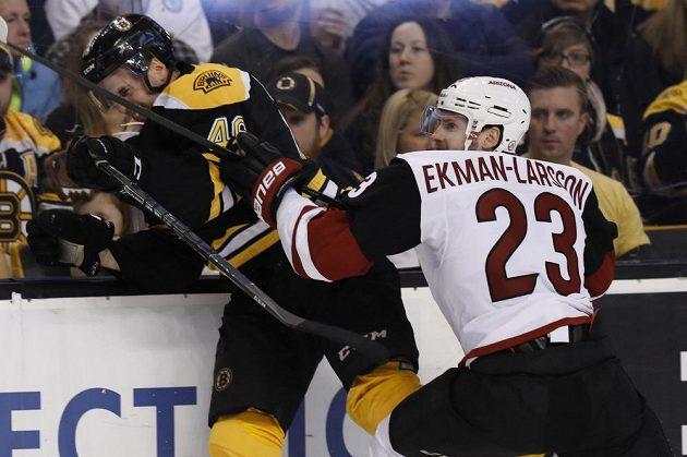 Obránce Arizony Coyotes Oliver Ekman-Larsson přišpendlil na mantinel českého útočníka Davida Krejčího z týmu Boston Bruins v utkání NHL.