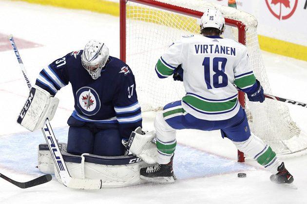 Brankář Winnipegu Connor Hellebuyck zastavuje šanci Jakea Virtanena.