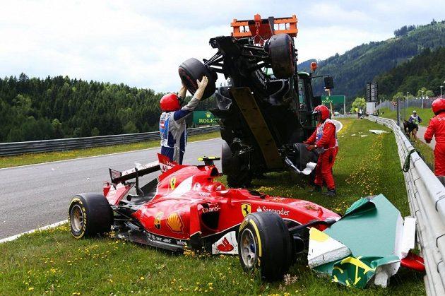 Organizátoři odklízí monopost Fernanda Alonsa, který přistál na ferrari Kimiho Räikkönena.