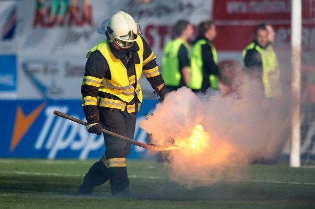 Hasič sbírá dýmovnici během utkání 6. kola Synot ligy Jablonec - Sparta.