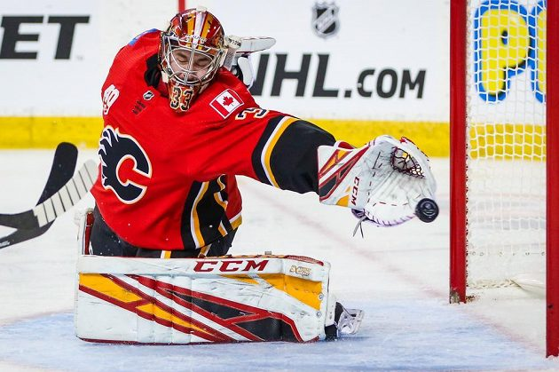 Český brankář Calgary Flames David Rittich (33) se natahuje po puku v utkání NHL.