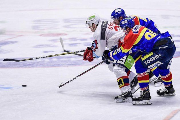 Pardubický hokejista Petr Sýkora se snaží prosadit v utkání baráže i extraligu. zastavit se jej snaží René Vydarený a Ondřej Kachyňa z Budějovic.