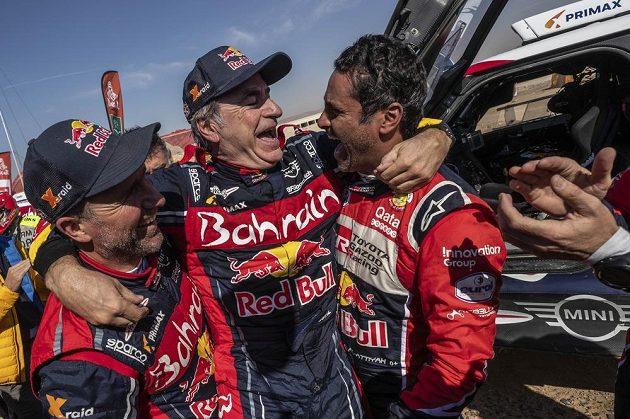 Španěl Carlos Sainz (uprostřed) přijímá gratulace od Francouze Stephane Peterhansela (vlevo) a Katařana Nassera Al-Attiyaha v cíli dakarské rallye.