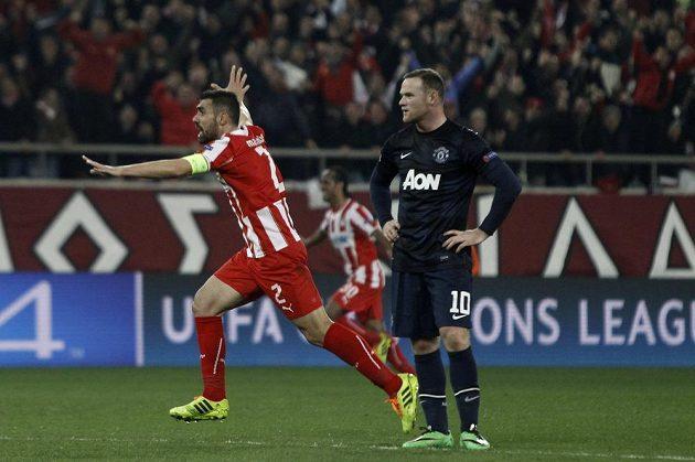 Giannis Maniatis (vlevo), kapitán Olympiakosu, jásá po gólu v síti Manchesteru United. Vpravo rozčarovaný Wayne Rooney.