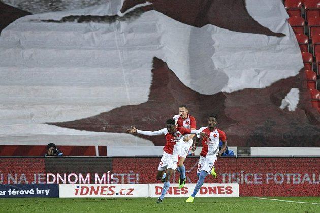 Hráči Slavie (zprava) Simon Deli a Jan Bořil se před prázdnou tribunou Sever radují z prvního gólu, který dal Ibrahim Traoré (vpředu).