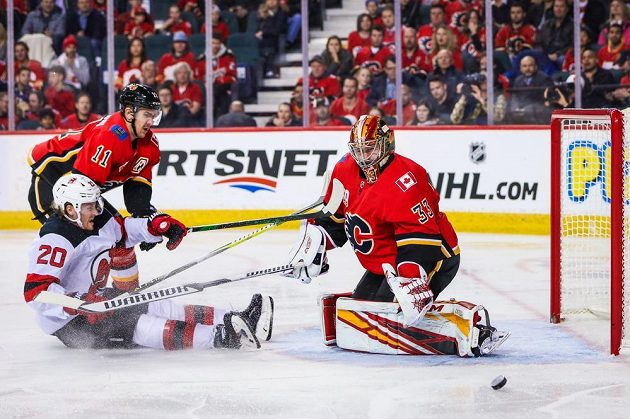 Brankář Calgary Flames David Rittich (33) vyrazil střelu v utkání NHL proti New Jersey.