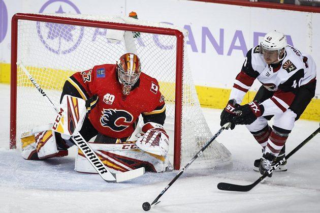 Hokjista Arizony Coyotes Michael Grabner se zkouší prosadit před brankou Davida Ritticha z Calgary.