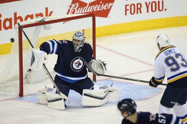 Brankář Winnipegu Ondřej Pavelec vyráží střelu útočníka St. Louis Scotta Gomeze.