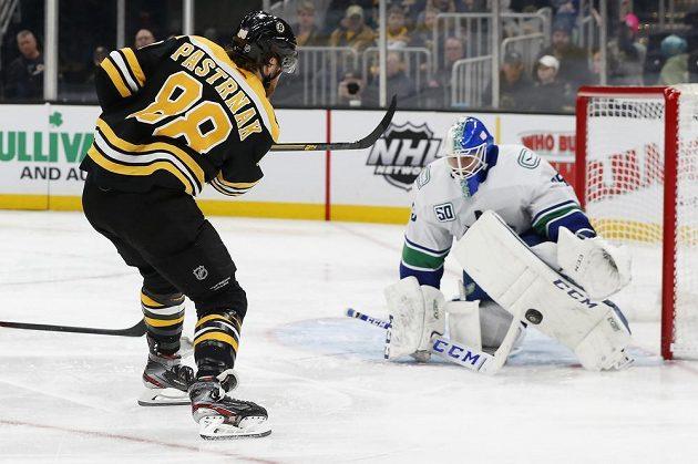 Brankář Vancouveru Canucks Jacob Markstrom zastavuje ránu českého útočníka Davida Pastrňáka z Bostonu v utkání NHL.