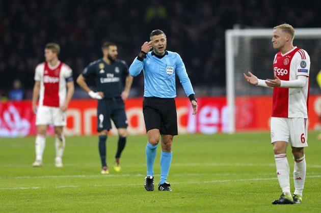 Fotbalisté Ajaxu diskutují s rozhodčím v utkání Ligy mistrů s Realem Madrid.