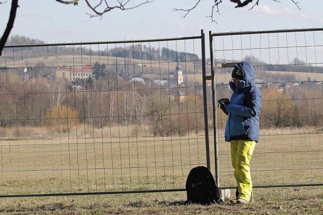 Dobrovolník u plotu kolem biatlonového areálu v Novém Městě na Moravě.
