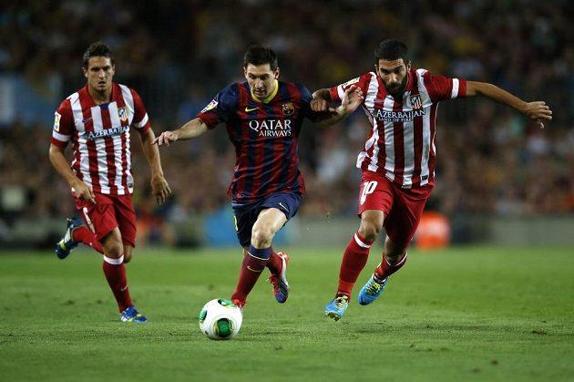 Barcelonský útočník Lionel Messi (uprostřed) uniká fotbalistovi Atlétika Madrid Ardu Turanovi.