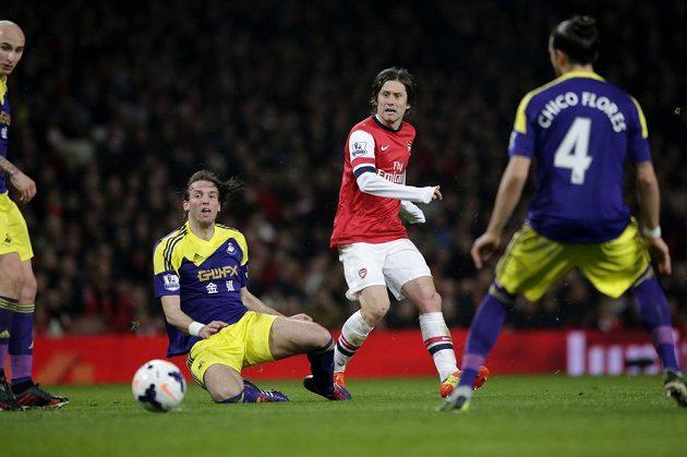 Záložník Arsenalu Tomáš Rosický (uprostřed) přihrává míč mezi hráči Swansea City Michuem (na zemi) a Chico Floresem.