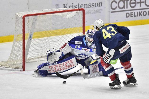 Brankář Brna Karel Vejmelka v akci, na jeho branku najíždí v utkání hokejové extraligy Antonín Dušek z Pardubic.