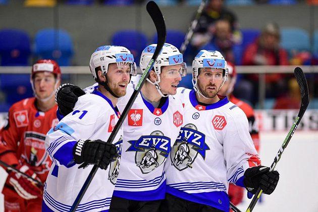 Hokejisté Zugu (zleva) Dario Meyer, Dario Simion a David Mcintyre oslavují gól v utkání Ligy mistrů v Hradci Králové.
